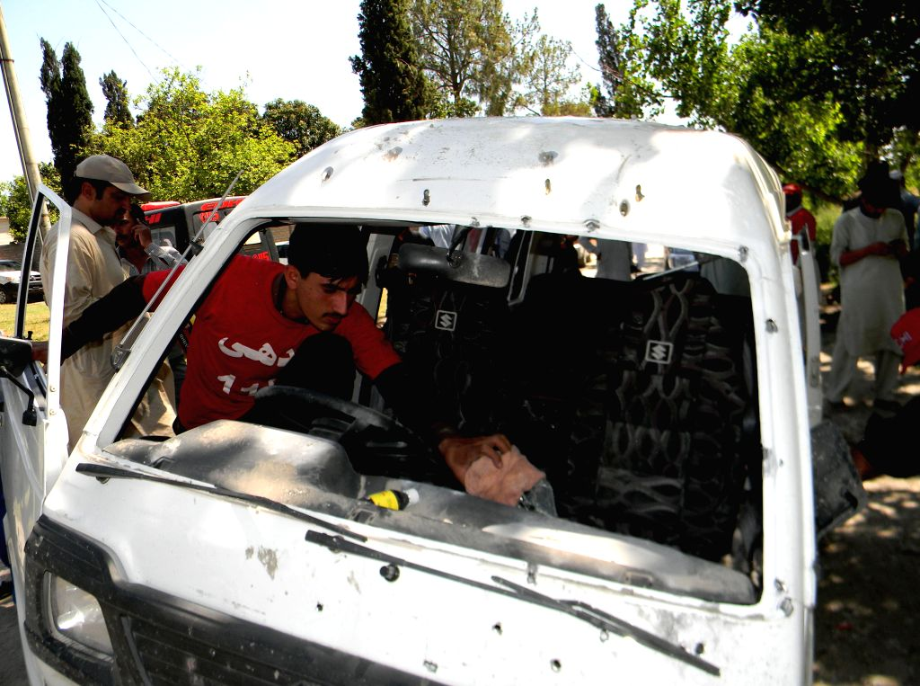 PESHAWAR, May 18, 2016 - A rescuer examines a damaged vehicle at the twin blasts site in northwest Pakistan's Peshawar, May 18, 2016. At least one policeman was killed and 14 others were injured when ...