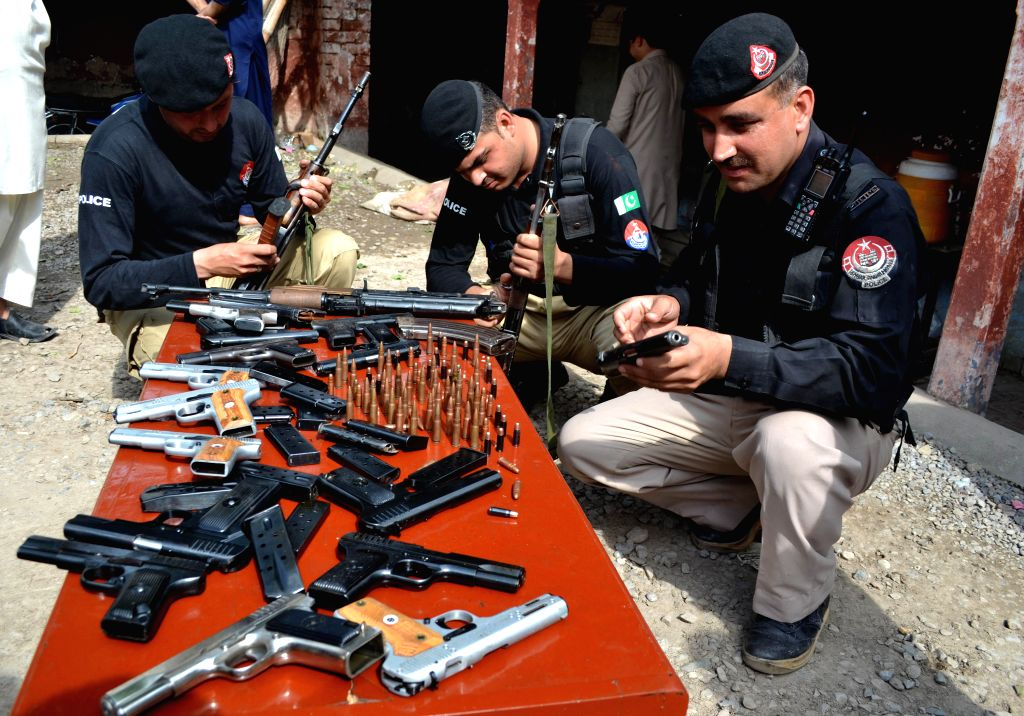 Policemen display seized weapons at a police station in northwest Pakistan's Peshawar, May 2, 2015. Pakistani police sized a huge amount of hashish and arrested two ...