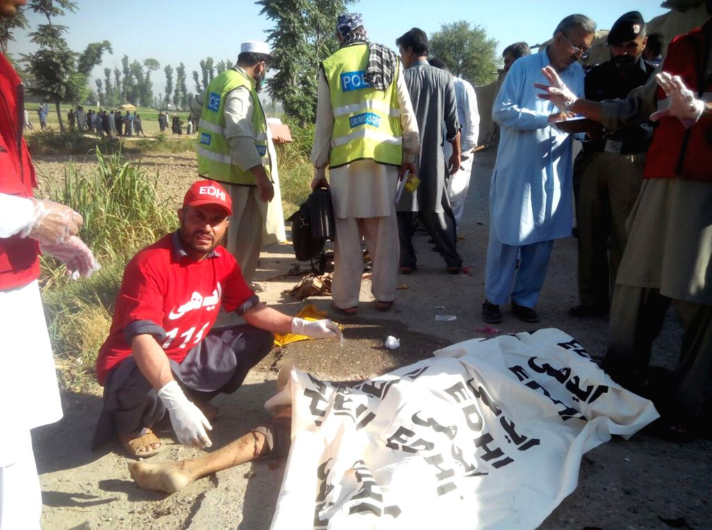 PESHAWAR, May 20, 2016 - A rescuer examines the body of a suspected suicide bomber at the blast site in northwest Pakistan's Peshawar, on May 20, 2016. At least three suicide bombers were killed on ...