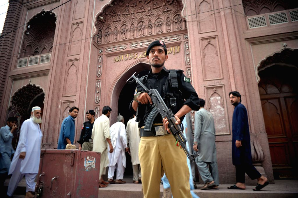 PESHAWAR, May 31, 2019 - A policeman stands guard as Pakistani Muslims walk to attend the last Friday prayers of the holy month of Ramadan at a mosque in Peshawar, northwest Pakistan, May 31, 2019.