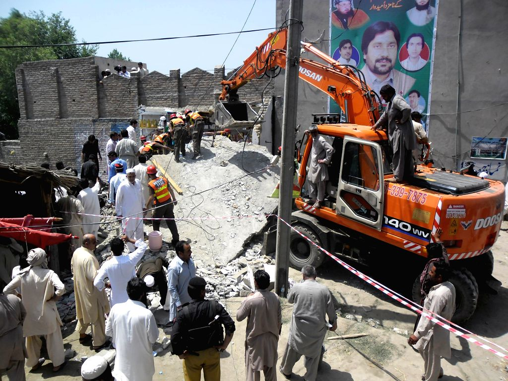 Rescuers and local residents search for survivors at a building collapse site in northwest Pakistan's Peshawar, May 4, 2015. At least one person was killed and two ...