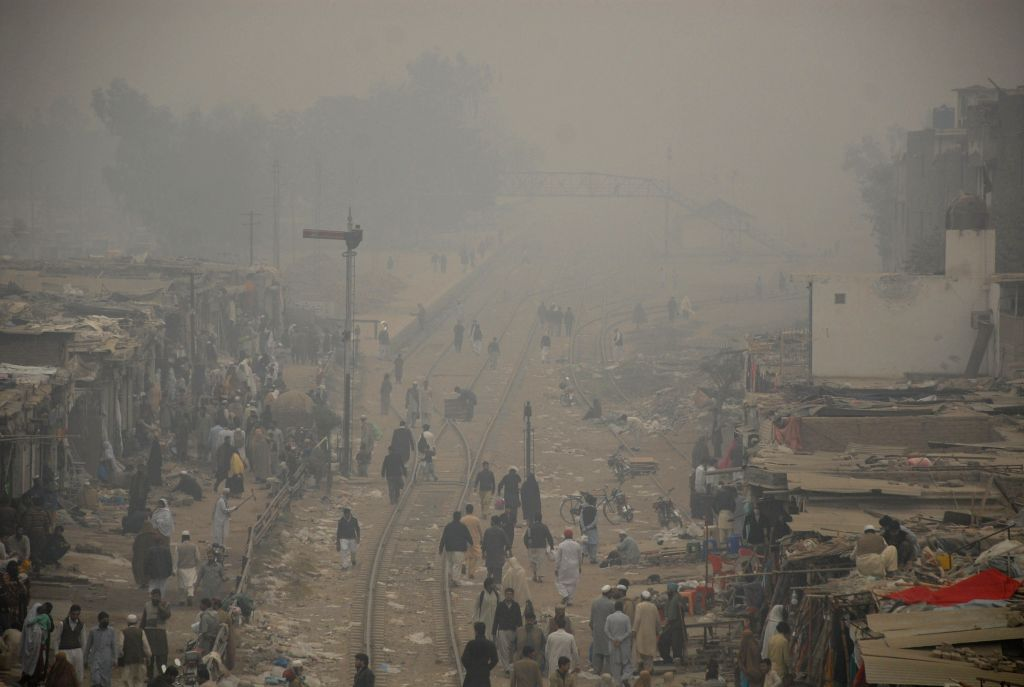 PESHAWAR, Nov. 23, 2016 - People walk at a bazaar in heavy smog in northwest Pakistan's Peshawar on Nov. 23, 2016. Heavy smog engulfed cities of Pakistan on Wednesday.