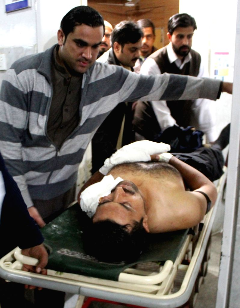 PESHAWAR, Nov. 28, 2016 - People transfer an injured man to a hospital in northwest Pakistan's Peshawar on Nov. 28, 2016. A policeman was killed and three others were injured after some unknown ...