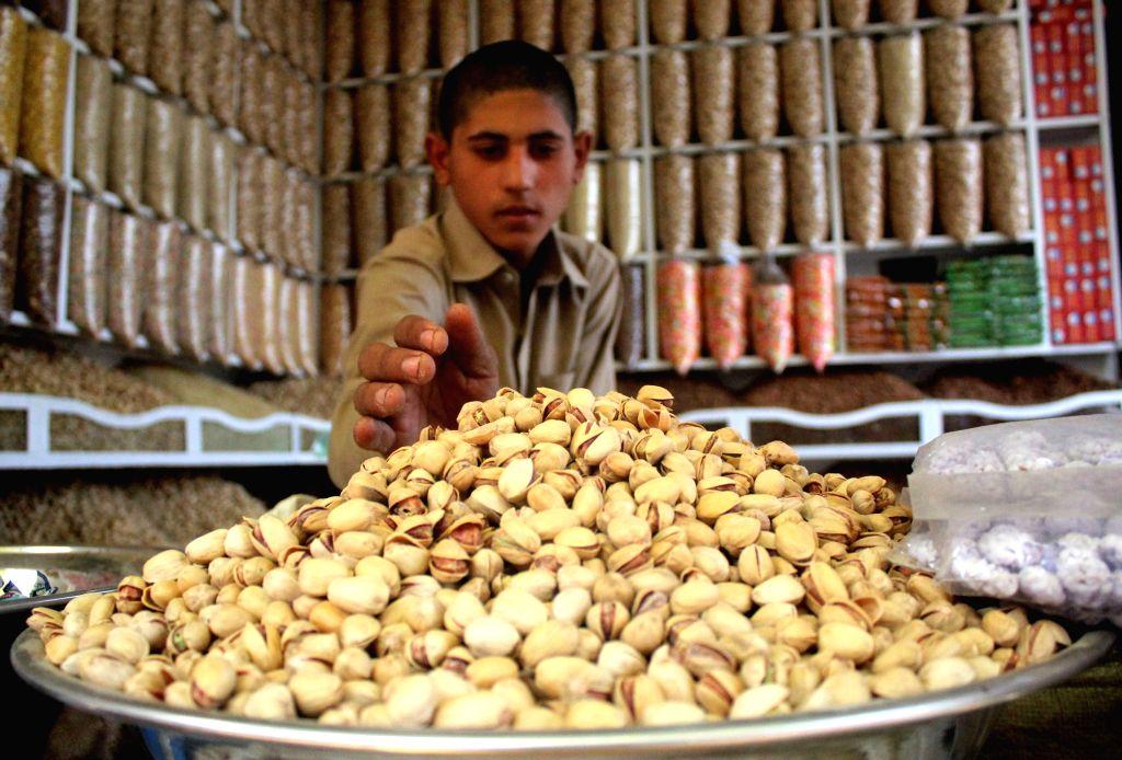 PESHAWAR, Oct. 23, 2016 - A Pakistani vendor arranges pistachios at a dried fruit market in northwest Pakistan's Peshawar, Oct. 23, 2016. Dried fruits are popular among Pakistani people in winter.