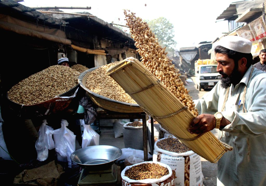 PESHAWAR, Oct. 23, 2016 - A Pakistani vendor cleans peanuts at a dried fruit market in northwest Pakistan's Peshawar, Oct. 23, 2016. Dried fruits are popular among Pakistani people in winter.