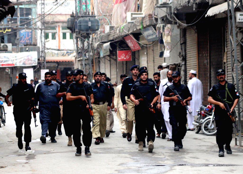 PESHAWAR, Oct. 8, 2016 - Pakistani policemen stand guard on a road ahead of Ashura, the 10th day of the Islamic month of Muharram, in northwest Pakistan's Peshawar, Oct. 8, 2016. Pakistani ...