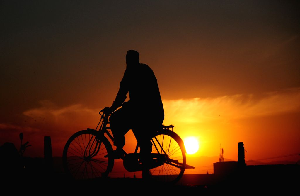 Peshawar (PAKISTAN), June 25, 2020 A cyclist is silhouetted against sunset in Peshawar, northwest Pakistan, on June 25, 2020.