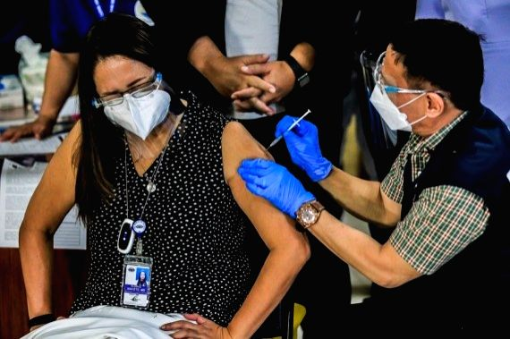 Philippine Department of Health Secretary Francisco Duque III injects a shot of COVID-19 vaccine from China's Sinovac to a doctor on the first day of the vaccination at the Lung Center ...