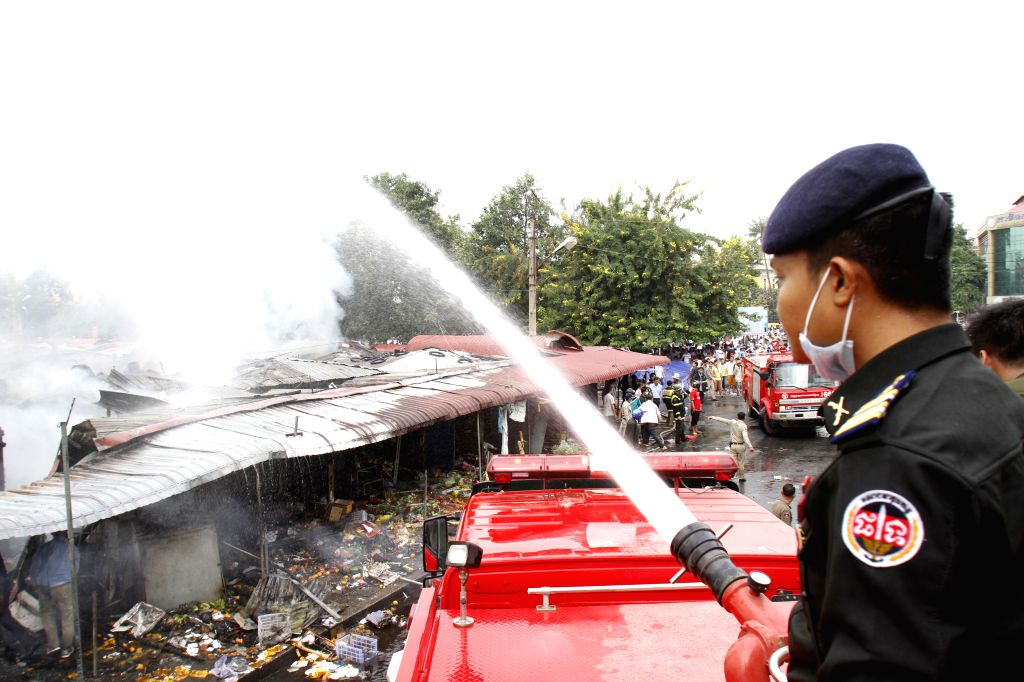 Phnom Penh: A fire fighter tries to extinguish fire at burning market in Phnom Penh, Cambodia, Nov. 24, 2014. A fire swept through the Old Market here in the capital city of Cambodia on Monday, ...