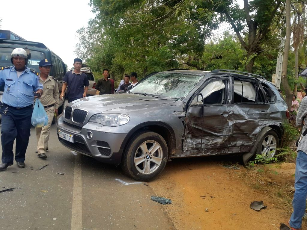 Photo provided by police shows people gathering around a badly damaged BMW car of Cambodian Prince Norodom Ranariddh in Kampong Cham province, Cambodia, on ...