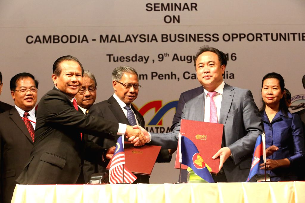 PHNOM PENH, Aug. 9, 2016 - President of the Cambodia Chamber of Commerce Kith Meng (R, front) shakes hands with Dzulkifli Mahmud (L, front), Chief Executive Officer of Malaysia External Trade ...