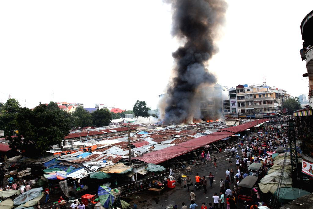 Phnom Penh: Fire and smoke engulf the Old Market in Phnom Penh, Cambodia, Nov. 24, 2014. A fire swept through the Old Market here in the capital city of Cambodia on Monday, completely destroying ...