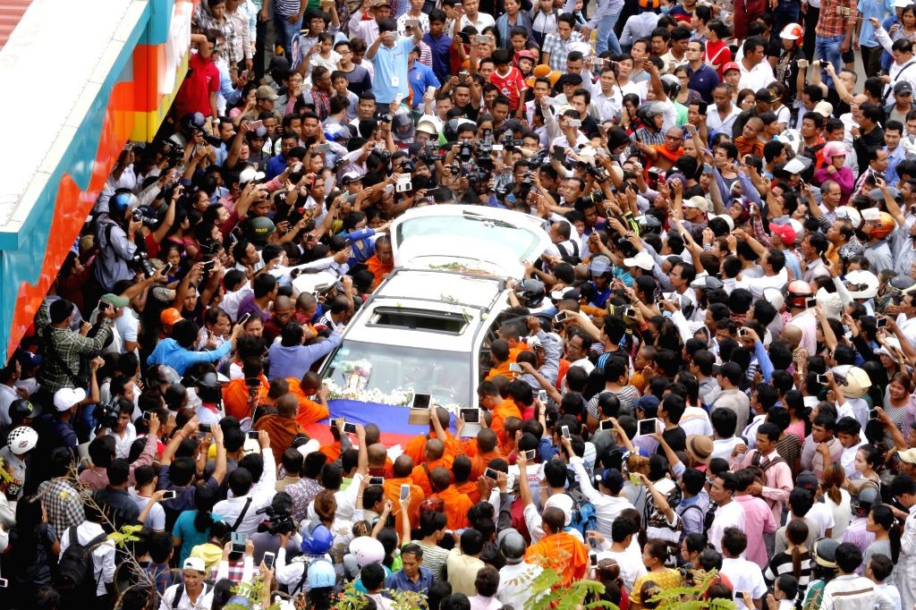 PHNOM PENH, July 10, 2016 - Bystanders take photos of the car carrying the body of political analyst Kem Ley in Phnom Penh, Cambodia, July 10, 2016. Cambodian Prime Minister Samdech Techo Hun Sen on ... - Samdech Techo Hun Sen