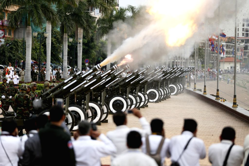Photo taken on July 11, 2014 shows 101-gun artilleries salute being fired at the riverside in front of the Royal Palace in Phnom Penh, Cambodia. Thousands of ...