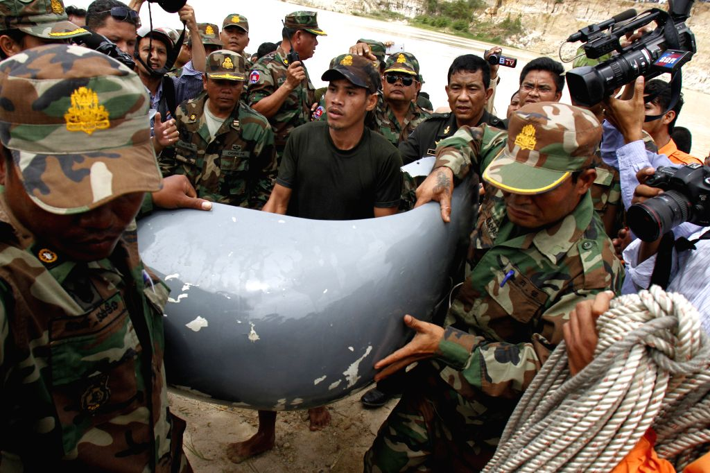 Rescue teams move a part of crashed military helicopter from water in Dangkor district on the outskirts of Phnom Penh, Cambodia, July 14, 2014. A Cambodian ...