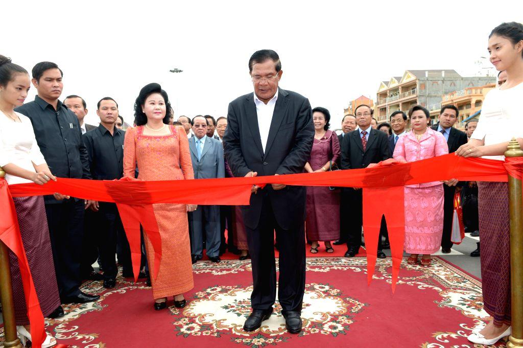 Cambodian Prime Minister Hun Sen (C) cuts the ribbon to inaugurate an overpass in Phnom Penh, Cambodia, July 31, 2014. Cambodian Prime Minister Hun Sen opened .. - Hun Sen