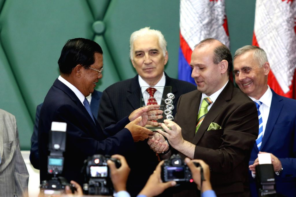 PHNOM PENH, June 22, 2016 - Cambodian Prime Minister Samdech Techo Hun Sen (L) receives an award from Professor Anton Caragea, president of the European Council on Tourism and Trade, in Phnom Penh, ... - Samdech Techo Hun Sen