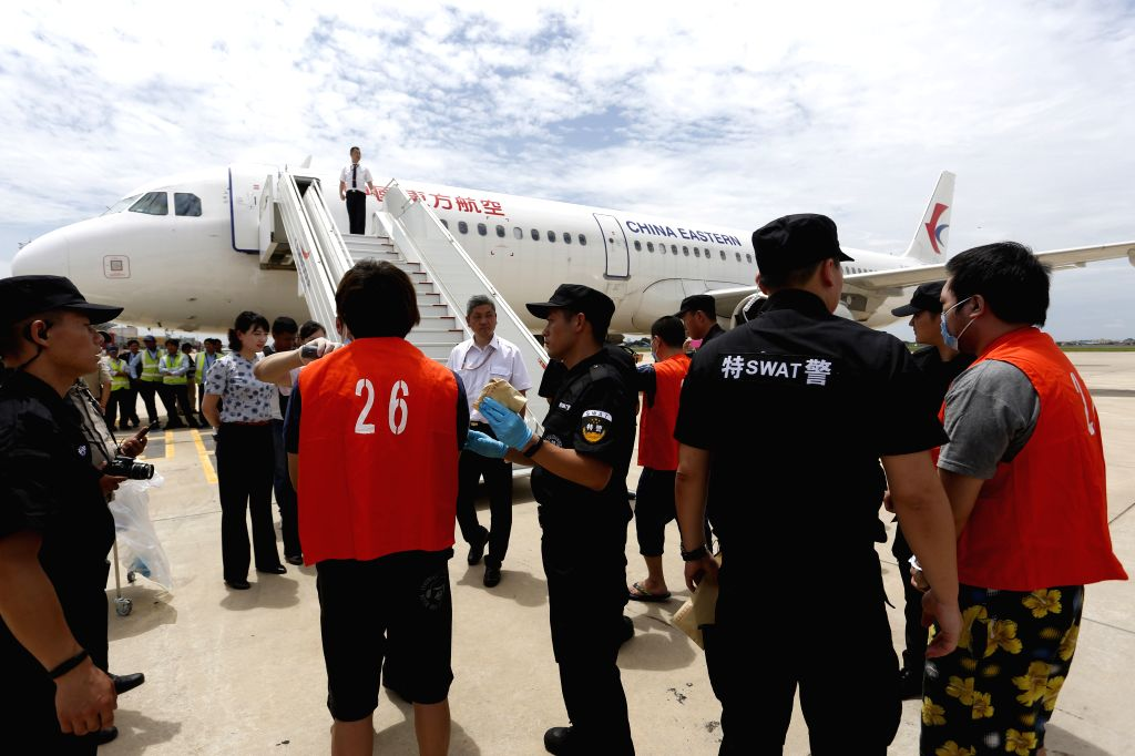 PHNOM PENH, June 24, 2016 - Chinese police officials frisk Chinese telecom fraud suspects at Phnom Penh international airport in Phnom Penh, Cambodia, June 24, 2016. Cambodia deported 39 Chinese ...