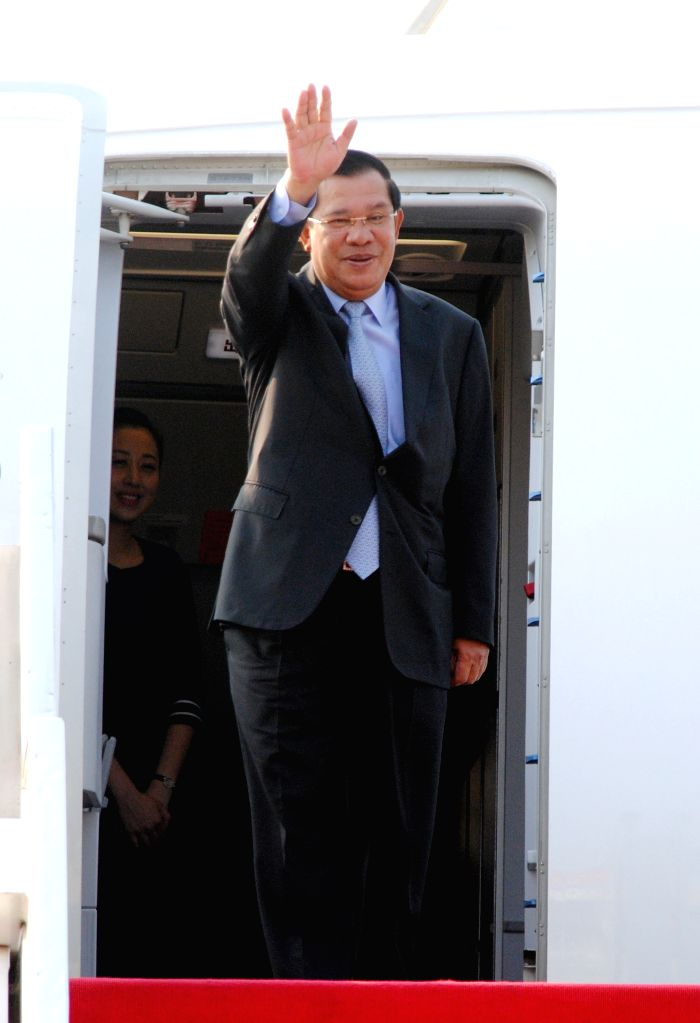 Cambodian Prime Minister Hun Sen gestures from the plane in Phnom Penh, Cambodia, March 13, 2015. Cambodian Prime Minister Hun Sen left for Sendai, Japan on ...
