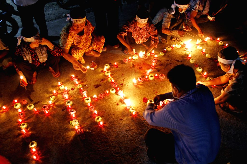 People light incense sticks and candles to pray for the