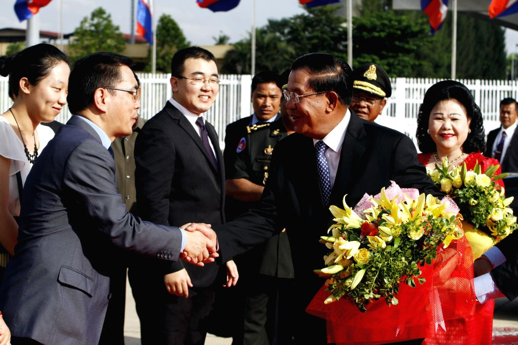 Cambodian Prime Minister Hun Sen (R, front) shakes hands with Li Zhigong (L, front), political counselor at the Chinese embassy in Cambodia, in Phnom Penh, ...