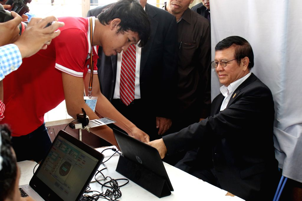 PHNOM PENH, Oct. 5, 2016 - Kem Sokha (R), deputy leader of the main opposition Cambodia National Rescue Party (CNRP), registers for upcoming elections at a voter registration center in Phnom Penh, ...