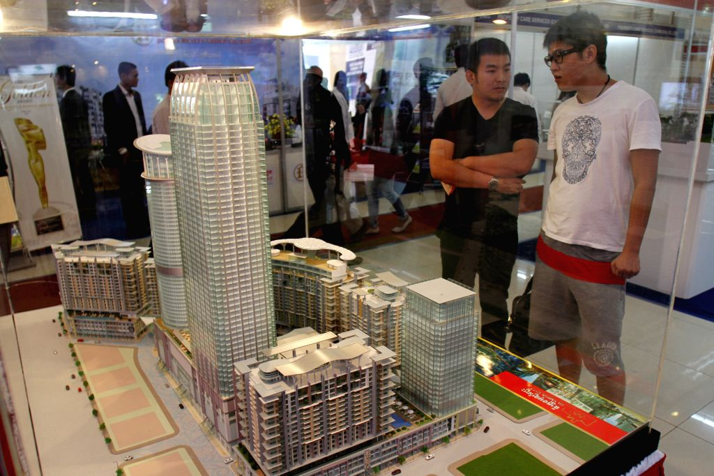 People visit architectural model buildings during an exhibition on Sept. 10, 2014 in Phnom Penh, Cambodia. An international construction and property ...