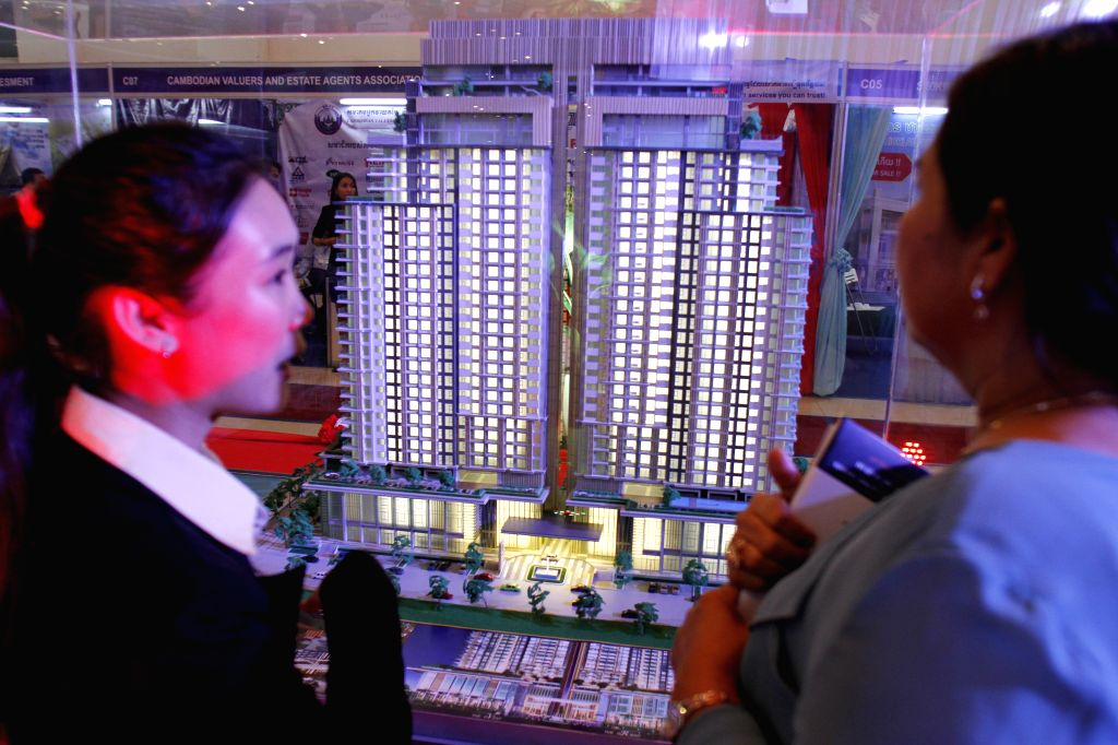 People watch architectural model buildings during an exhibition on Sept. 10, 2014 in Phnom Penh, Cambodia. An international construction and property ...