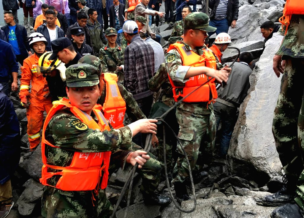 Photo taken by a cellphone shows rescuers working at the accident site after a landslide occurred in Xinmo Village of Maoxian County, Tibetan and Qiang Autonomous ...