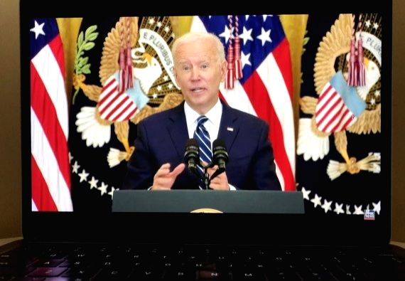 Photo taken in Arlington, Virginia, the United States, on March 25, 2021 shows a screen displaying U.S. President Joe Biden speaking during a press conference in Washington, D.C., in a live stream ...