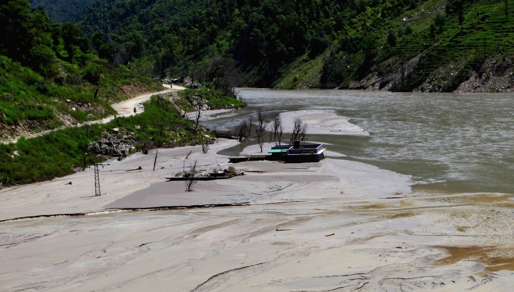 Photo taken on Aug. 2, 2015 shows the remains of houses trapped in a dam formed in Sunkoshi River after the massive landslide occurred a year ago on Aug. 2, ...