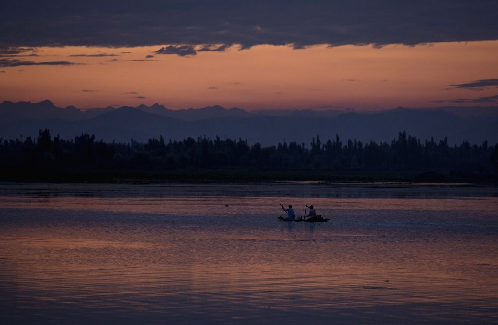 Photo taken on Aug. 29, 2020 shows boatmen rowing their boat during sunset at Dal Lake in Srinagar, the summer capital of Indian-controlled Kashmir.