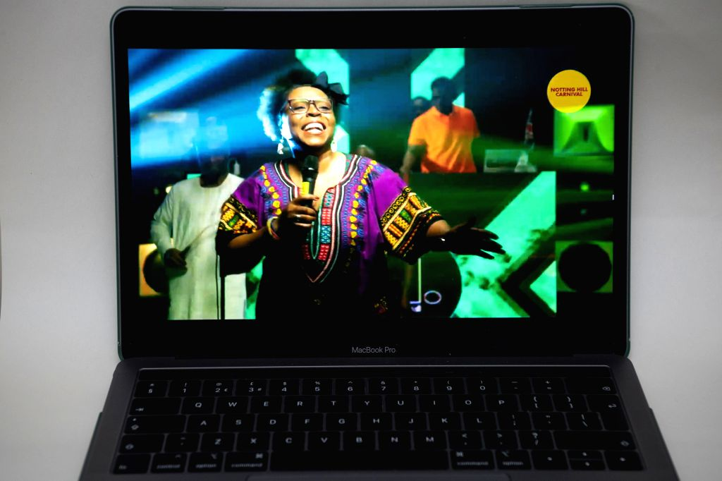 Photo taken on Aug. 30, 2020 in London, Britain shows a laptop's screen showing the online content of the Notting Hill Carnival. The Notting Hill Carnival, an annual ...