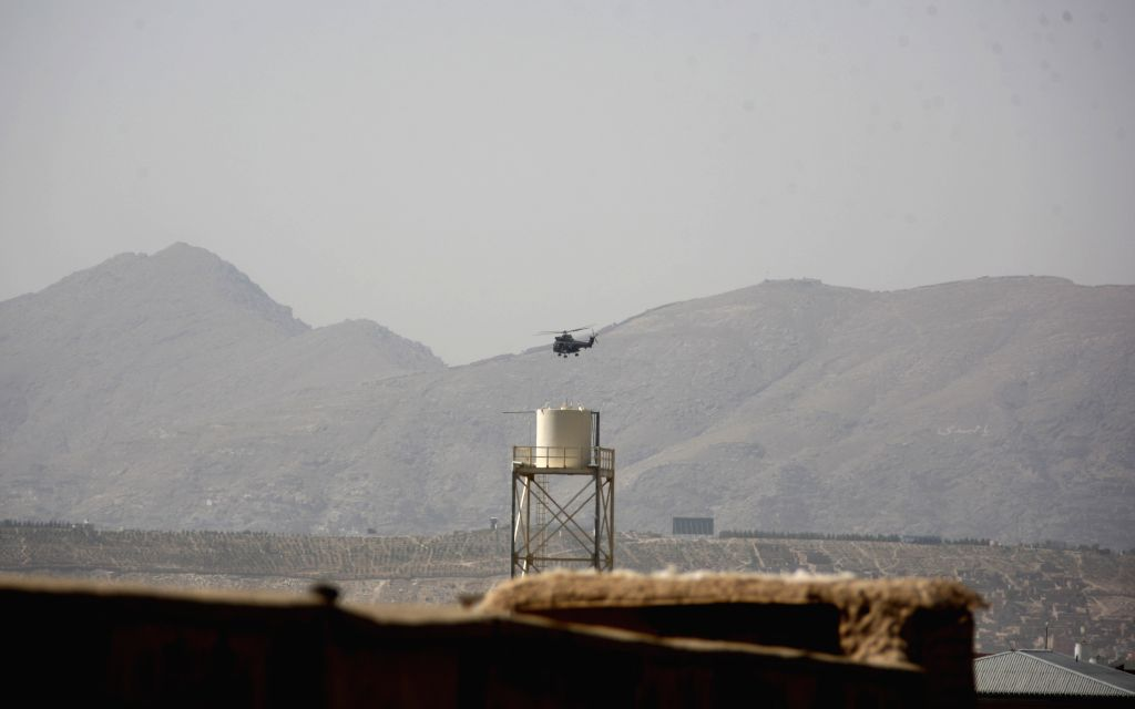 Photo taken on Aug. 8, 2015 shows a military helicopter flying over the sky close to a foreign compound following an attack by Taliban in Kabul, Afghanistan. The ...