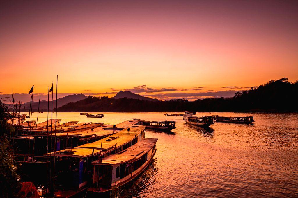 Photo taken on Jan. 1, 2020 shows the sunset scenery of Luang Prabang on the riverside of Mekong River, Laos. Luang Prabang, located aside the Mekong River, ...