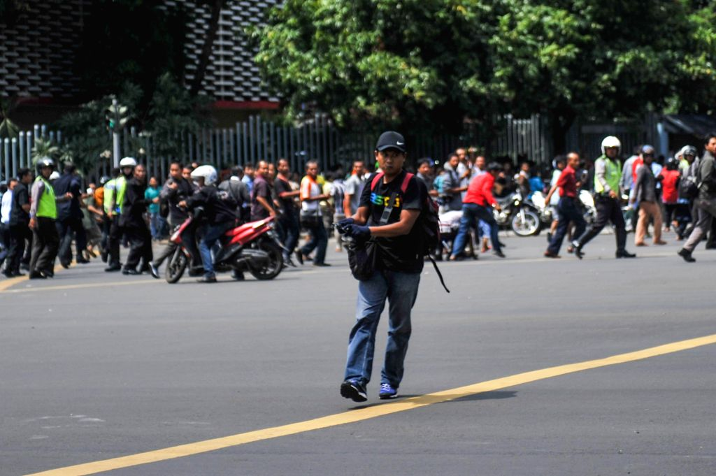 Photo taken on Jan. 14, 2015 shows a suspect terrorist with a gun at Thamrin street in Jakarta, Indonesia. At least six explosions were heard in the shopping mall ...