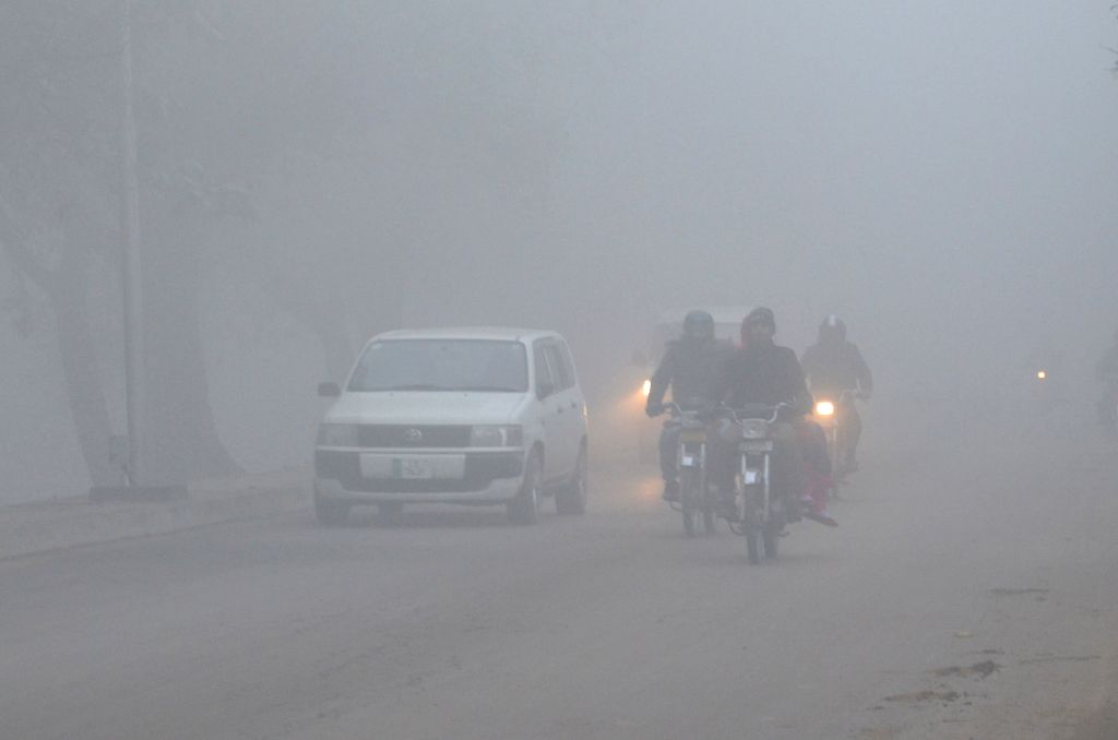 Photo taken on Jan. 14, 2016 shows vehicles moving on the road in heavy fog in eastern Pakistan's Lahore.