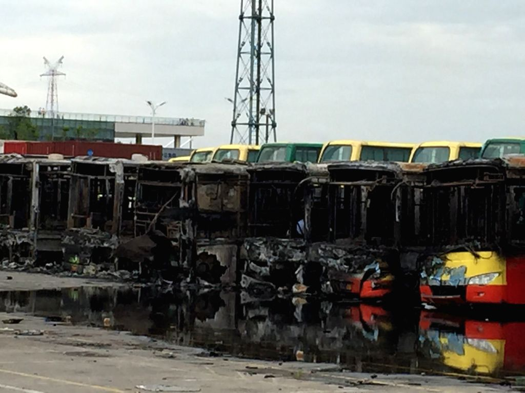 Photo taken on July 22, 2015 shows burnt-out buses at a bus depot after a fire took place in Huli District of Xiamen City, southeast China's Fujian Province. One ...