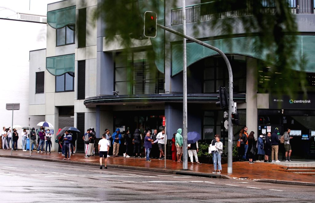 Photo taken on March 24, 2020 shows people lining up outside Centrelink in Sydney, Australia.   The COVID-19 outbreak in the Australian State of Victoria will likely ...