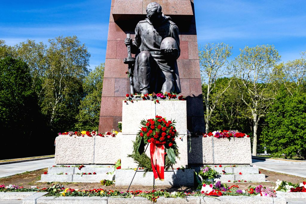 Photo taken on May 8, 2020 shows a wreath and flowers by a statue of a Soviet soldier at the Soviet Memorial in Treptower Park in Berlin, capital of Germany. People ...