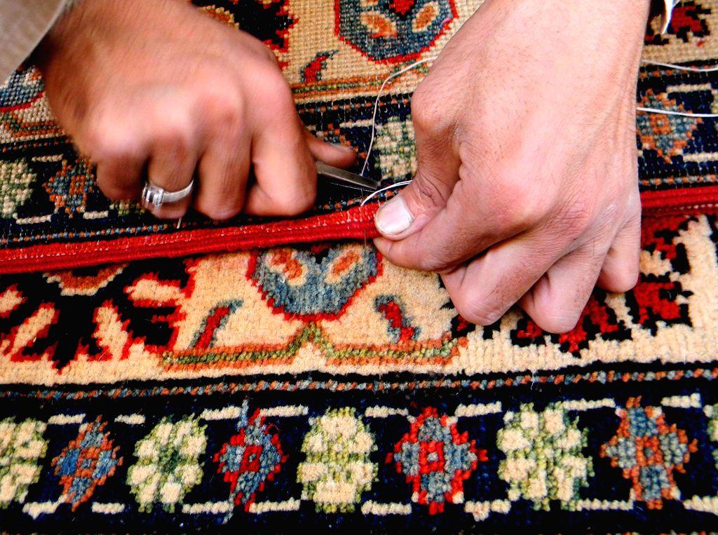 Photo taken on Nov. 16, 2015 shows a Pakistani man making handmade carpets at a factory on the outskirts of northwest Pakistan's Peshawar. (Xinhua/Ahmad ...