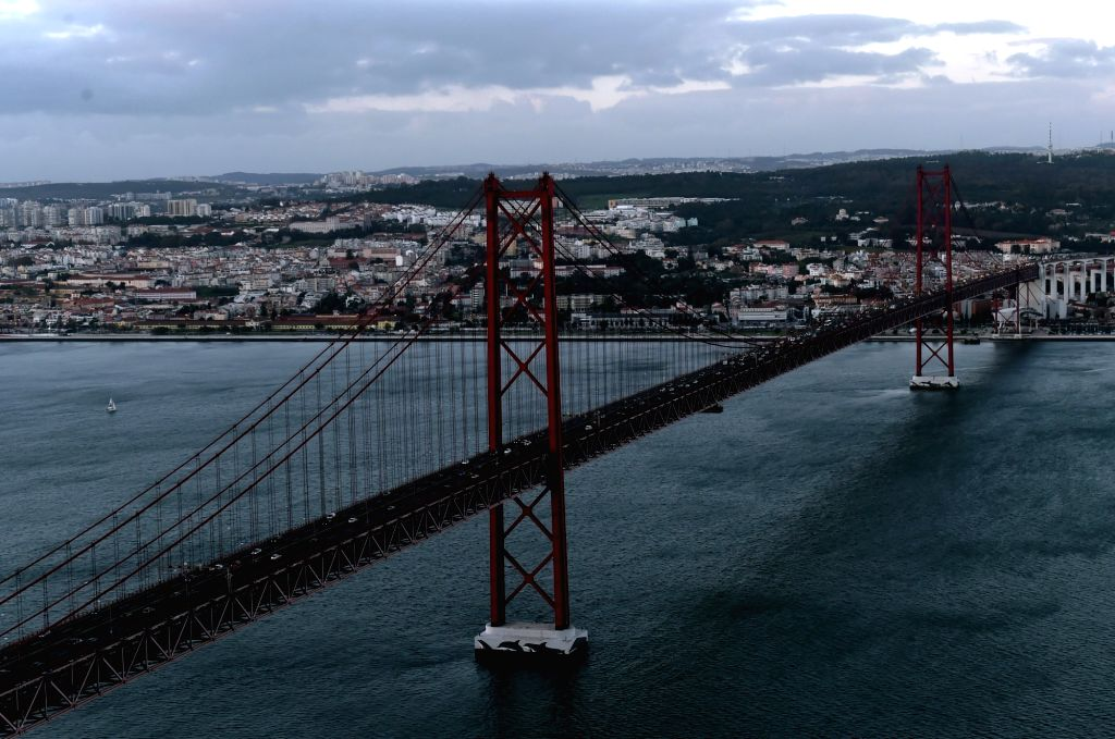 Photo taken on Nov. 21, 2015 shows 25 de Abril Bridge (25th of April Bridge) connecting Lisbon to Almada across the Tejo River, in Lisbon, capital of Portugal. ...