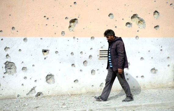 Photo taken on Sept. 29, 2020 shows a man walking by a house damaged during clashes in the Tartar district bordering the Nagorno-Karabakh region.