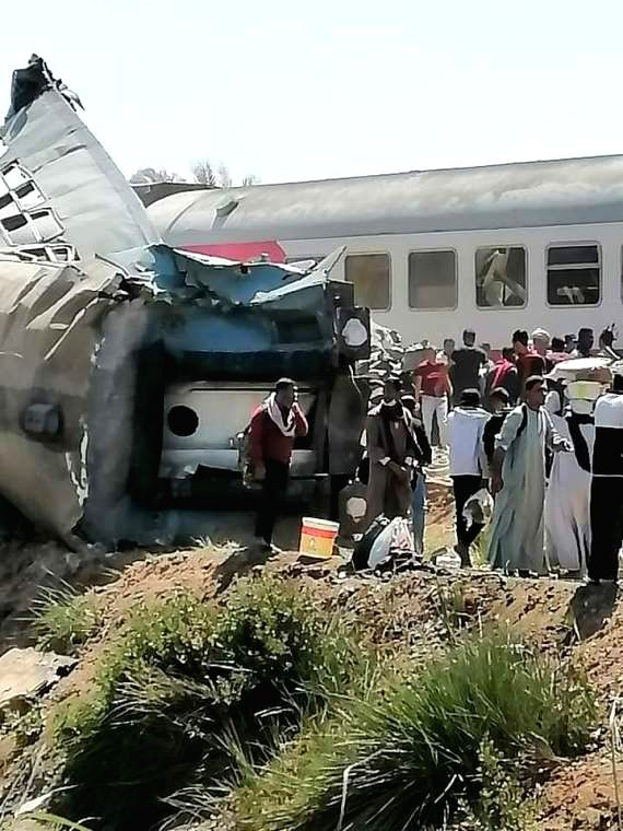 Photo taken with a mobile phone on March 26, 2021 shows people gathering at the site of a train collision in Sohag, Egypt. (Photo by Ahmed al-Afyouni/Xinhua)