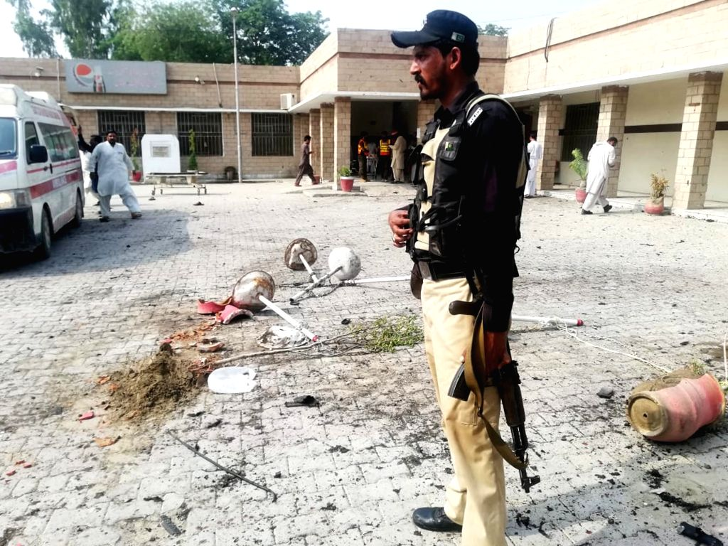 Photo taken with a mobile phone shows a policeman standing guard at the blast site in northwest Pakistan's Dera Ismail Khan on July 21, 2019. A string of ... - Dera Ismail Khan