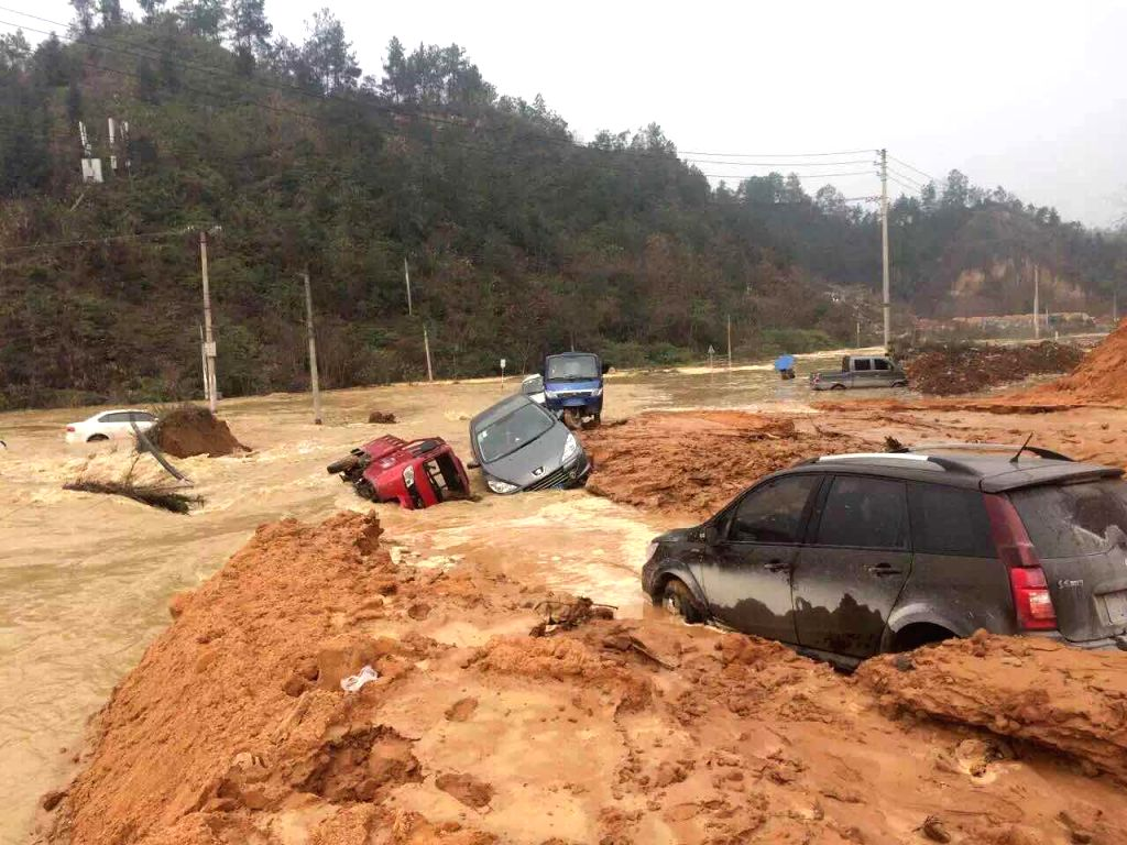 Photo taken with a mobile phone shows flooded vehicles after the dike of a barrier lake collapsed in Longfeng Township of Enshi Tujia and Miao Autonomous Prefecture, ...