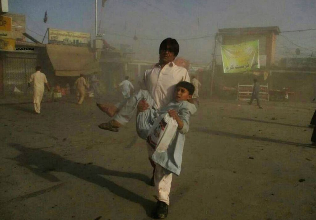 Photo taken with mobile phone shows a man helps an injured child near a blast site in northwest Pakistan's Parachinar, on June 23, 2017. At least 18 people were killed and over 100 others ...