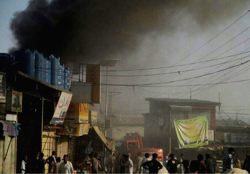 Photo taken with mobile phone shows local people gather as smoke rises from a blast site in northwest Pakistan's Parachinar, on June 23, 2017. At least 18 people were killed and over 100 ...