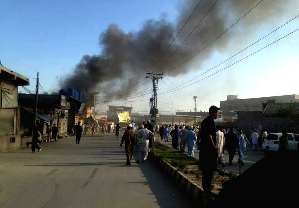 Photo taken with mobile phone shows smoke rises from a blast site in northwest Pakistan's Parachinar, on June 23, 2017. At least 18 people were killed and over 100 others injured as twin ...