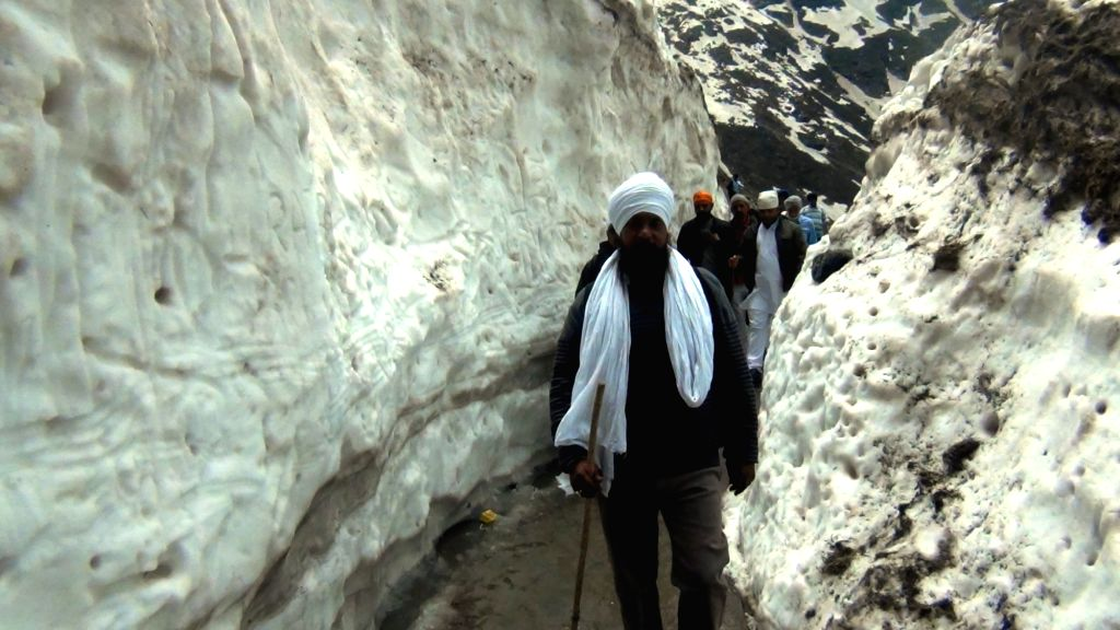 Pilgrims pass through a narrow road with snow on both sides on their way to Hemkund Sahib in Chamoli district of Uttarakhand on May 26, 2017.